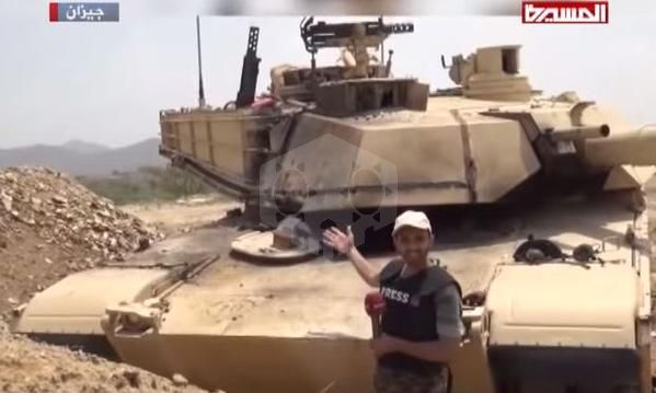파일:external/defence-blog.com/An-Al-Masirah-reporter-and-Houthis-stand-next-to-a-captured-Saudi-M1-Abrams-tank-1.jpg
